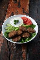 Falafel, vegan roasted chickpeas patties with garlic yogurt sauce on rustic wooden table