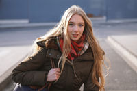 candid street style portrait of teenage girl waiting at bus stop