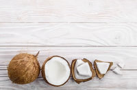 Flat lay background of coconut, coconut shell and meat pieces on white wooden table
