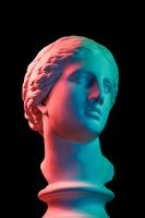 Gypsum copy of ancient statue Venus head isolated on black background. Plaster sculpture woman face. Multi color toned.