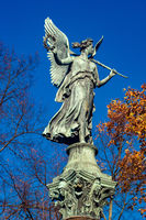 statue of an angel on a column in bright sunshine