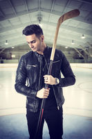 Handsome young man with a hockey stick
