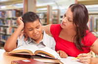 Upset Hispanic Young Boy and Famle Adult Studying At Library