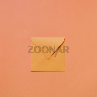 Empty handmade mock up envelope on a peach color background .