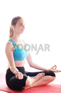 Young happy woman doing yoga sitting meditation. Healthy lifestyle concept. Place for text