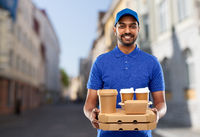 indian delivery man with food and drinks in city