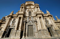 Exterior facade of Cathedral Catholic Church of Saint Mary front view against blue sky background, ancient architecture religious monument in Murcia city,  Spain