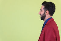 Closeup profile view of young happy bearded Persian businessman in suit smiling