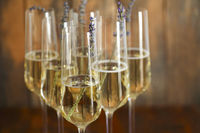 Glasses of champagne decorated with lavender on wooden background
