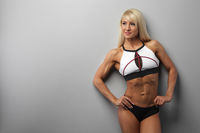 athletic beautiful blonde girl wears sportswear against a gray wall