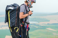 Close-up of a professional paraglider with a cocoon on his shoulders buttons helmet looks to the side. Paraglider sport concept