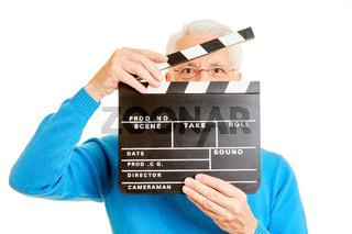 Mann als Regisseur schaut durch Filmklappe