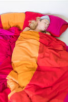 Blonde woman sleeping in her colorful bed.