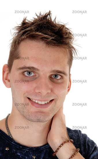 Smiling young man standing with hand on neck