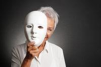happy senior woman peeking from behind mask
