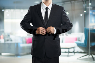 Smart businessman in black suit with button up pose  .