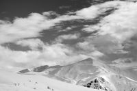 Black and white ski slope and sky with clouds in evening