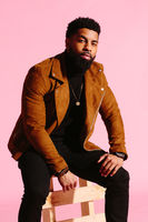 Stylish, handsome and cool African American man with beard, isolated on pink studio background