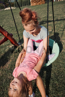 Sisters having fun on a swing together