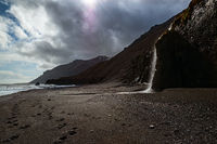 Waterfall in a black beach in Iceland