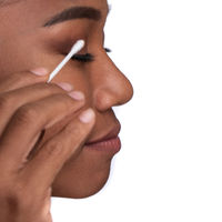 Close-up portrait of a beautiful woman cleaning her face with cotton swab bud isolated on white background.