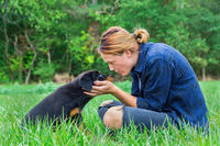 Woman loving rottweiler puppy in nature