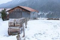 Firewood near a barn and house