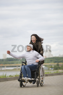 Cheerful woman with young disabled man in wheelchair running on the quay
