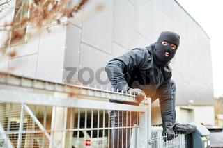 Einbrecher steigt über Zaun von Industrie Firma