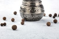 Allspice, Jamaican pepper. Black peppercorns with a vintage pepper mill, close-up with a place for text