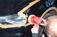 Car mechanic polishes the paint on the vehicle
