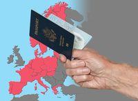 Man holding US passport on map of Schengen Zone