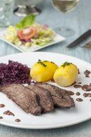 deutscher Sauerbraten mit Rotkohl auf dem Teller