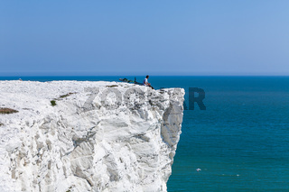 Young man on rock and enjoying beautiful view, male sitting on edge, bicycle lying down cliff by sea. Summer holidays recreation watching sunset glowing