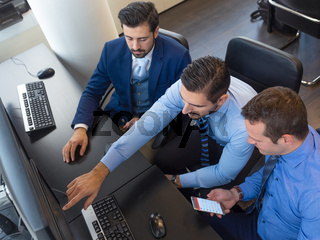 Business team analyzing trade data on computer in corporate trading office.