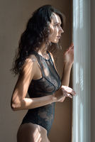 Sexy woman in black lace underwear looking to the window.