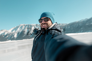 tourist make selfie on frozen lake with monutains in background