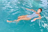 Junge Frau schwimmt auf dem Rücken