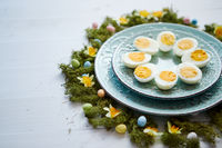 Easter table setting with flowers and eggs. Decorative plates with boiled eggs