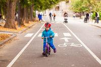 Happy boy of three years riding on balance bike in autumn