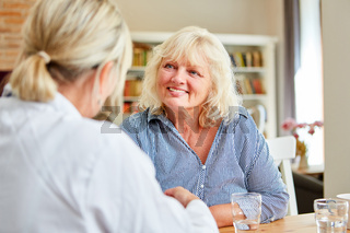 Pflegedienst Frau und Seniorin bei Hausbesuch