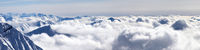 Panorama of snowy mountains covered with sunlight clouds at winter