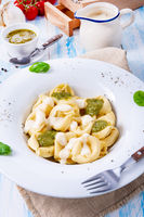 Tortellini di formaggio with basil pesto and cheese sauce