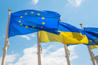 Flagpoles with European Union and Ukraine flags on blue sky background