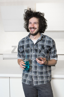 Handsome man using a mobile phone in kitchen