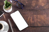 Working table with smart phone notepad coffee cup pen glasses plant on wooden