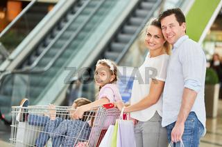 Familie schiebt Kinder im Einkaufswagen