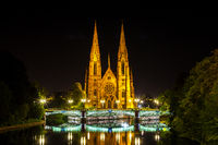 View at the historic church of Saint Paul with the river Ill in Strasbourg at night, Alsace, France