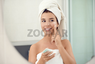 Pretty young woman in white towels in a bathroom