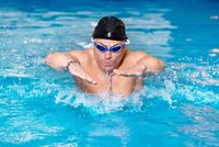 Muscular swimmer young man in black cap in swimming pool, performing butterfly stroke.